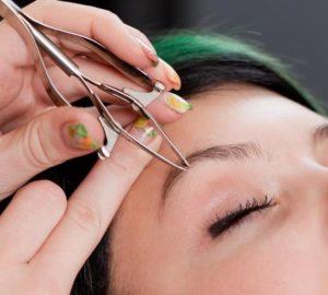 Epilation des sourcils à l'aide d'une pince à épiler